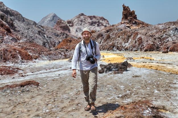 Un uomo caucasico turistico sorridente cammina da attrazioni naturali con la macchina fotografica, hormuz, hormozgan, iran.