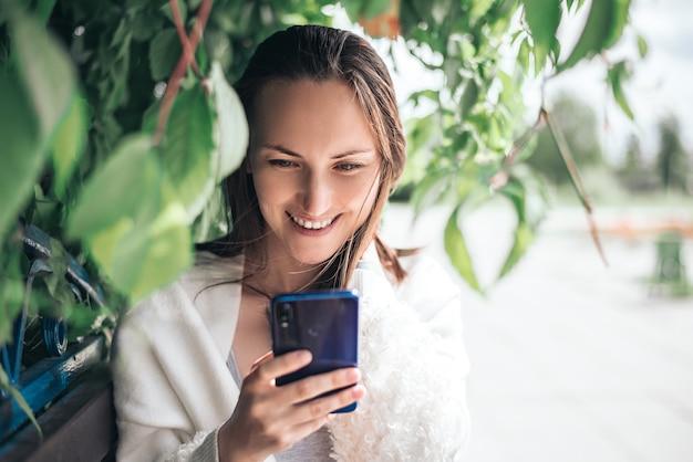 Una donna sorridente con lo smartphone in mano seduto su una panchina tra le foglie