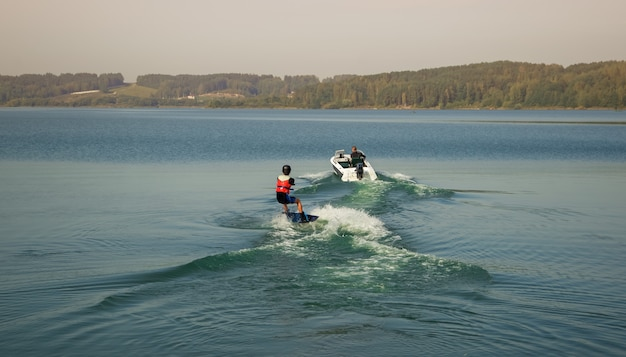 Un wakeboarder sportivo cavalca dietro una barca