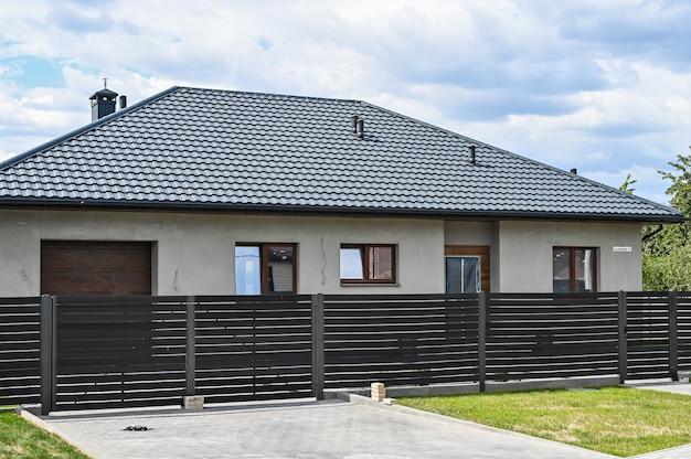 Casa a un piano con tetto grigio e recinzione