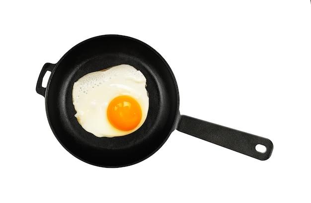 Un uovo fritto sul lato soleggiato su una padella in ghisa nera con manico