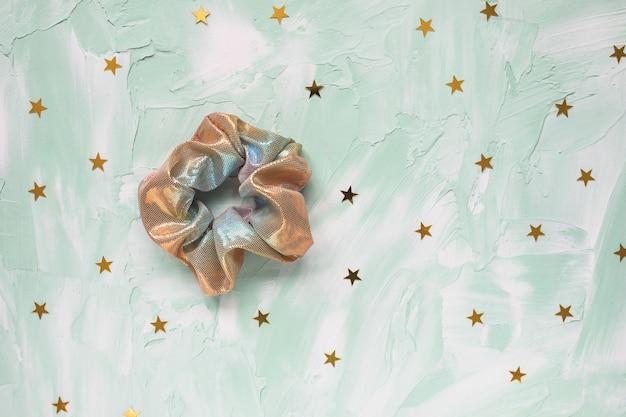 Un trendy olografico iridiscente metallizzato lucido scrunchy e coriandoli di stelle dorate sul verde