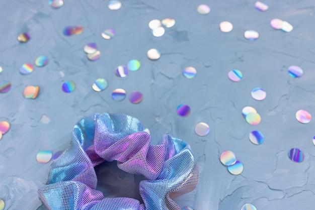 Un trendy olografico iridiscente metallizzato lucido scrunchy e coriandoli argento metallizzato su superficie blu.