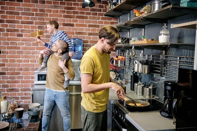 Uno dei due uomini gay che cucinano ai fornelli contro il marito che gioca con un ragazzo