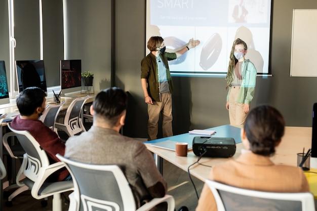 Uno dei due giovani designer con maschere protettive che punta al nuovo modello di smartwatch sulla lavagna mentre fa una presentazione ai colleghi