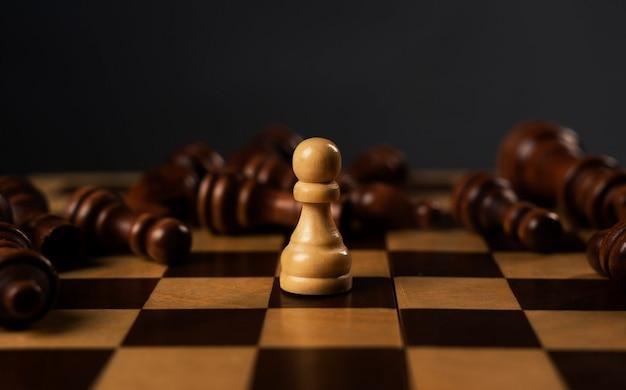 Un pedone bianco è il vincitore tra i pezzi degli scacchi neri caduti sulla scacchiera