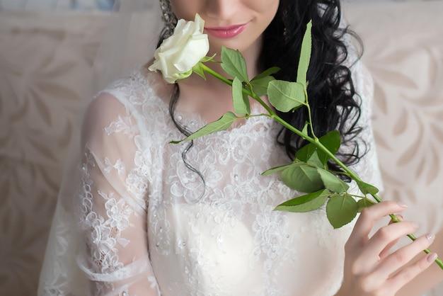 Una rosa bianca nelle mani della sposa il giorno del matrimonio