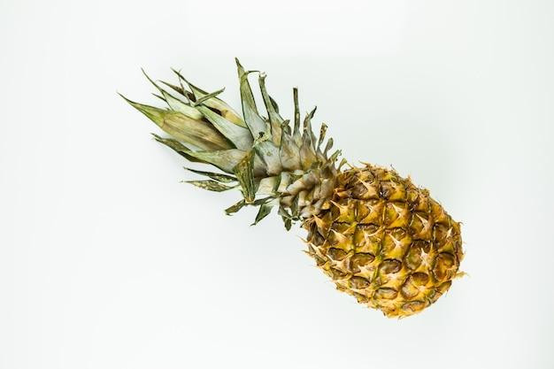 Un intero ananas su sfondo bianco isolato. vista dall'alto di ananas fresco maturo posa sul tavolo bianco