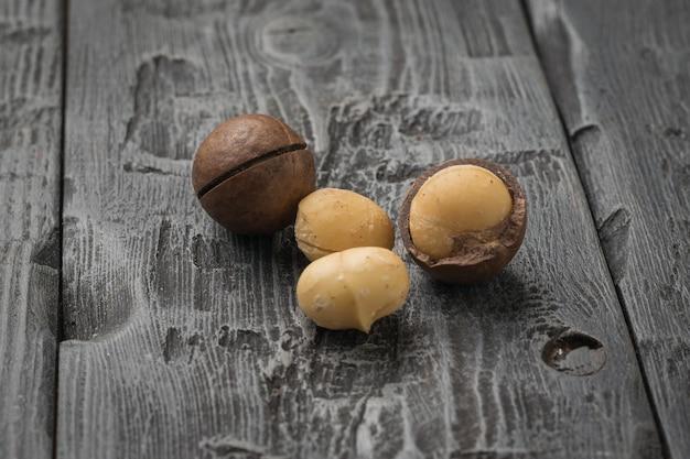 Un intero e tre noci di macadamia sbucciate su un tavolo di legno. superfood.