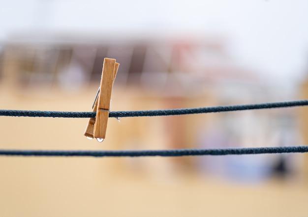 Una molletta da bucato in legno su una corda blu con gocce d'acqua appese dopo la pioggia con spazio di copia.