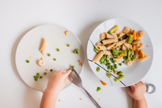 Il bambino di un anno mangia il cibo dal suo piatto direttamente con le mani.