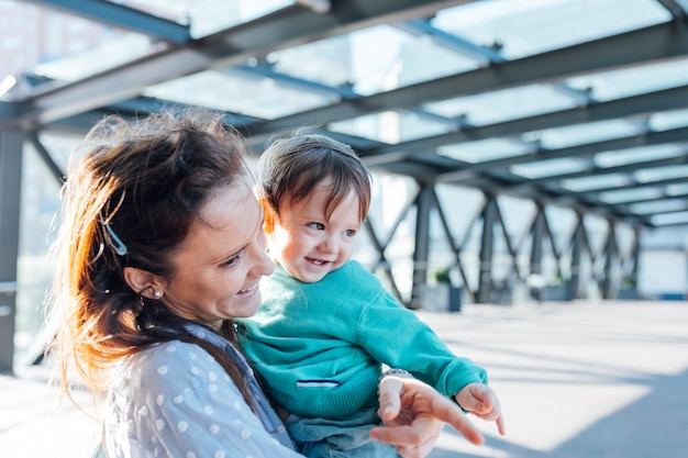 Bimbo di un anno dallo sguardo malizioso che sorride sorpreso dalla madre millenaria per strada