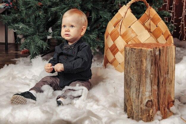 Un bambino di un anno su una soffice coperta bianca che gioca vicino all'albero di natale. ragazzo carino nel soggiorno decorato di natale. piccolo bambino che guarda lontano. concetto di bambini felice anno nuovo. copia spazio per il sito
