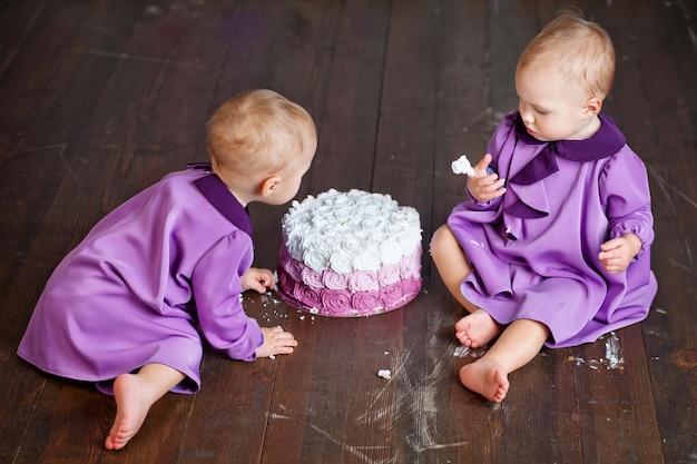 Due gemelle di un anno festeggiano il loro primo compleanno e mangiano torta.