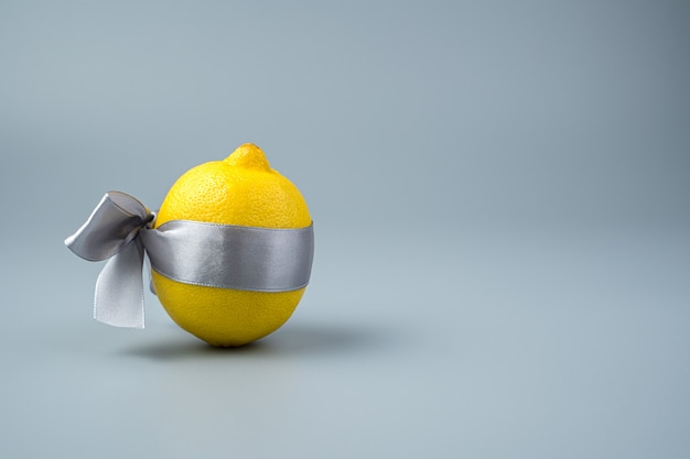 Un limone giallo in un nastro grigio satinato su sfondo grigio.