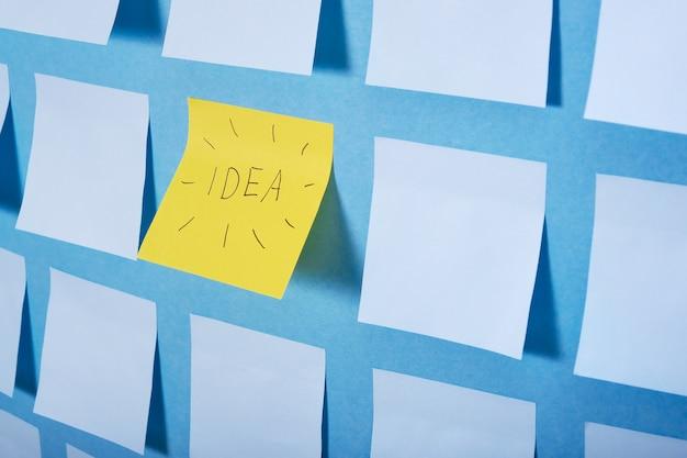 Un adesivo giallo con l'idea di iscrizione tra il set di adesivi di carta azzurra su sfondo blu