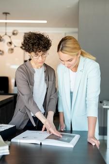 Una delle giovani donne di affari fiduciose che mostra l'immagine sulla pagina del libro spesso mentre consulta il collega
