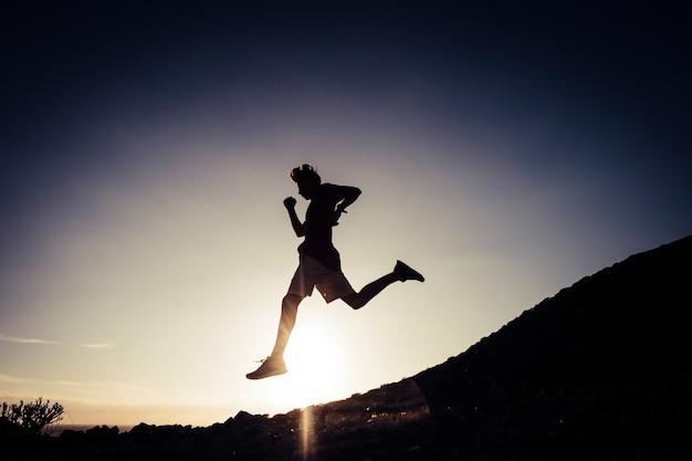 Un giovane che corre e fa esercizio da solo nel parco o in montagna perde peso e si prende cura del suo corpo e della sua salute. adolescente attivo che fa jogging e fa esercizi di routine