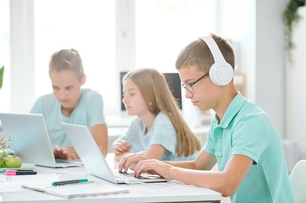 Uno dei giovani compagni di classe in cuffia guardando il display del laptop mentre si guarda il video online dalla scrivania
