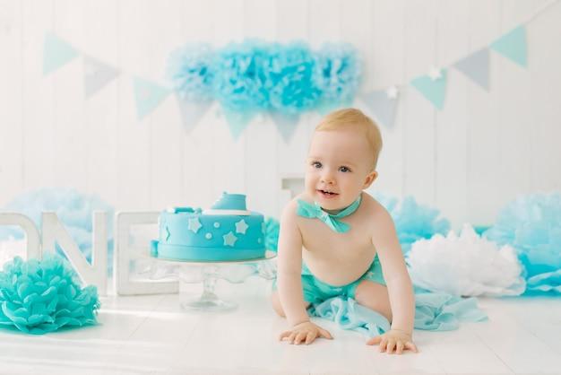 Un bambino di un anno con una farfalla è a quattro zampe sullo sfondo di una zona fotografica