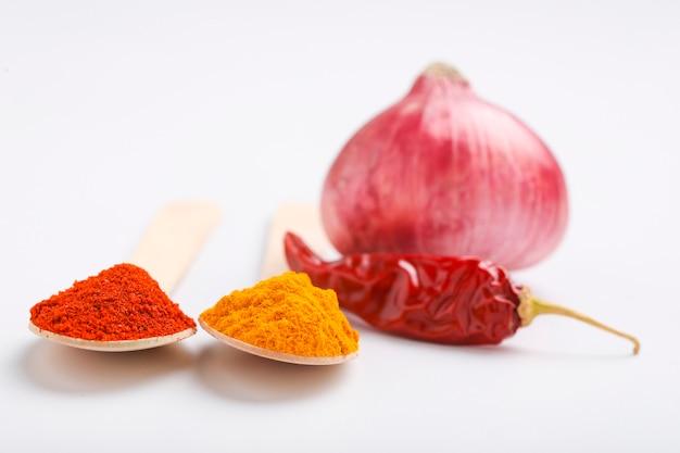 Cipolla, peperoncino rosso, peperoncino rosso in polvere e curcuma in polvere sulla superficie bianca