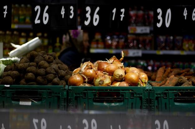 Cipolle, barbabietole e altri prodotti giacciono sul bancone del mercato alimentare insieme ai cartellini dei prezzi.