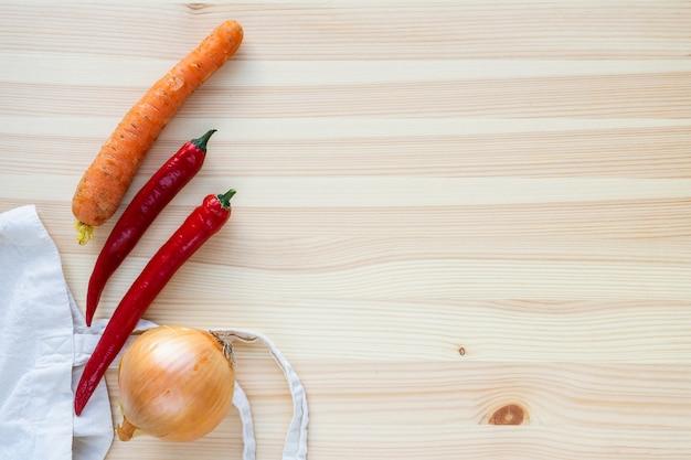 Cipolle, peperoni e carote su una vista dall'alto di un tavolo in legno