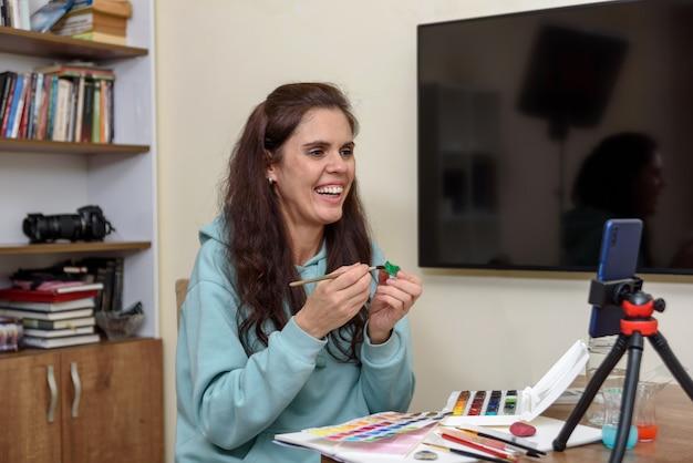 Lezione d'arte online durante la quarantena. smartphone con treppiede da vicino, l'insegnante parla di spazzole nell'interno della casa sfocate