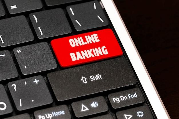 Operazioni bancarie in linea sul pulsante rosso di invio sulla tastiera nera.