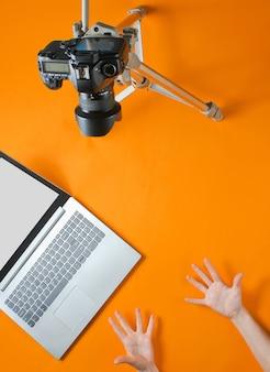 Concetto di blogger online. revisore di emoticon. le mani delle donne mostrano emotivamente il blog con? amera su treppiede, laptop su sfondo arancione. minimalismo.