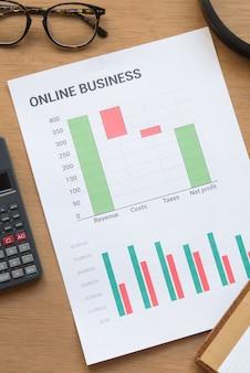 Grafici di affari in linea con calcolatrice e bicchieri