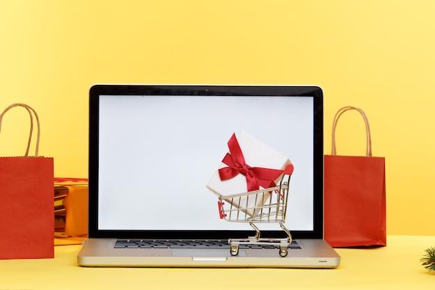 Carrello di acquisto di natale in linea sul computer portatile