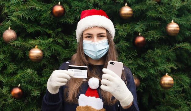 Shopping natalizio online. close up ritratto di donna che indossa un cappello di babbo natale e mascherina medica con emozione. sullo sfondo di un albero di natale. pandemia di coronavirus