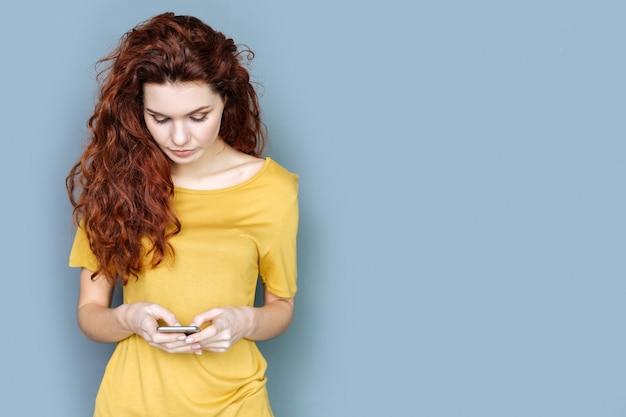 Comunicazione in linea. bella piacevole donna dai capelli rossi che tiene il suo smartphone e digita un messaggio mentre chatta con i suoi amici