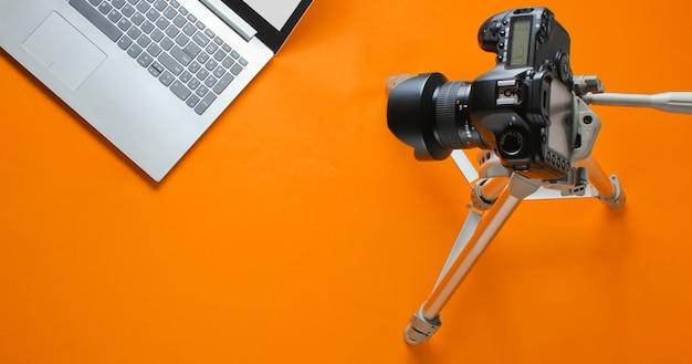 Concept blogger online, revisore. fotocamera su treppiede, laptop su sfondo arancione. minimalismo.