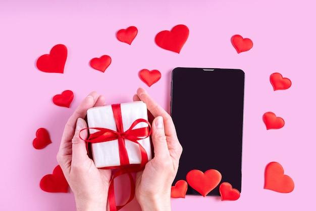 Concetto di congratulazioni online. le mani tengono un regalo con un nastro rosso su un tablet vuoto nero