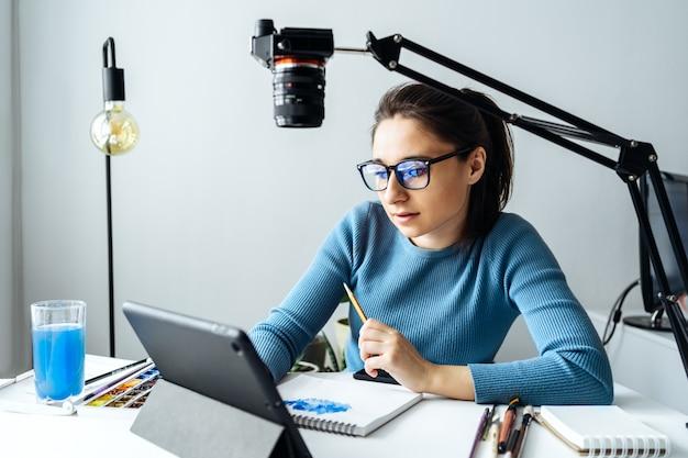 Vlogger di creatori di contenuti online. una giovane blogger con gli occhiali rimuove i contenuti per il blog, i corsi di formazione. il concetto di apprendimento online per attingere a walercolor