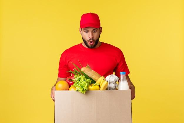 Shopping con consegna online e concetto di ordine di cibo corriere stupito ed eccitato in uniforme rossa su yello...