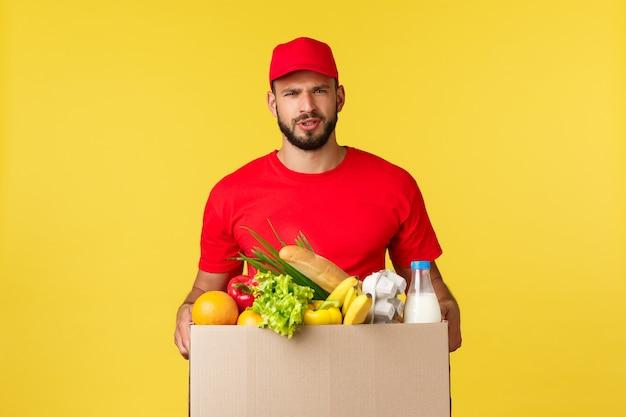 Consegna online shopping e concetto di ordine alimentare corriere dubbioso e sconvolto in uniforme rossa cap e ts...