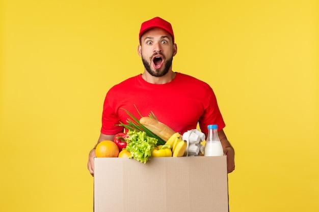 Consegna online shopping e concetto di ordine di cibo corriere eccitato e divertito in uniforme rossa barba del...