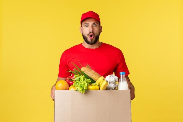 Lo shopping di consegna online e il concetto di ordine di cibo hanno impressionato il corriere barbuto in maglietta rossa con cappuccio uniforme ...