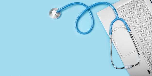 Consulto medico online, ospedale virtuale e terapia online. lo stetoscopio si trova sulla tastiera del laptop su sfondo blu