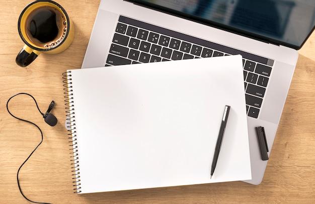 Concetto di istruzione online taccuino in bianco con il computer portatile, il caffè della tazza e il microfono sulla vista di legno del piano d'appoggio