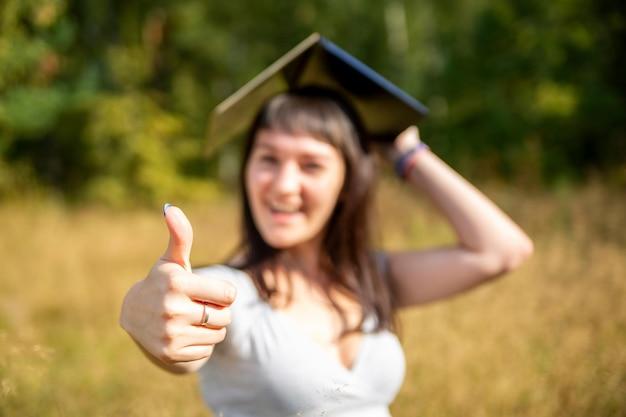 Il concetto di educazione online pollice in su sullo sfondo in sfocatura la giovane studentessa felice tiene un laptop