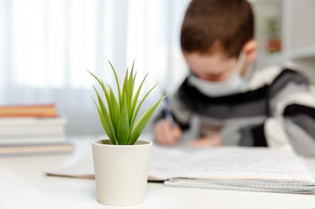 Formazione online e apprendimento a distanza. scolaro di malattia nella maschera medica che fa i compiti della scuola a casa