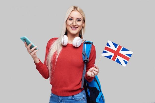 Formazione online, traduttore di lingua straniera, inglese, studente - donna bionda sorridente in cuffia con cellulare e bandiera britannica. spazio grigio, apprendimento a distanza
