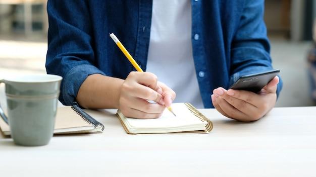 Formazione in linea di apprendimento, lavoro da casa, scrittura a mano dell'uomo sul notebook durante l'utilizzo del telefono cellulare