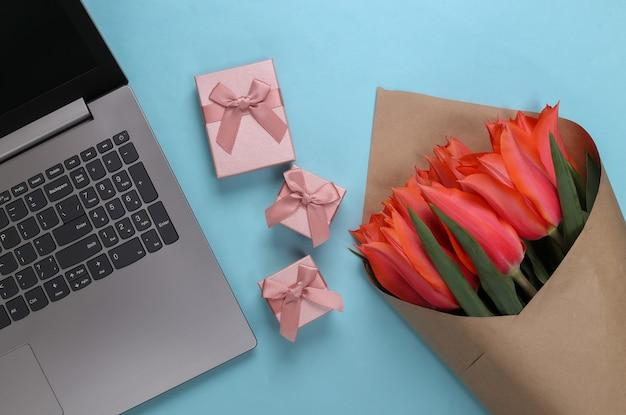 Negozio di fiori online. mazzo di tulipani con laptop e scatole regalo su blu