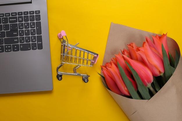 Negozio di fiori online. mazzo di tulipani con laptop, carrello del supermercato su giallo