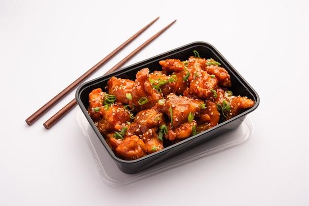 Concetto di consegna di cibo online in india - gustoso pollo al peperoncino confezionato in una scatola di plastica nera